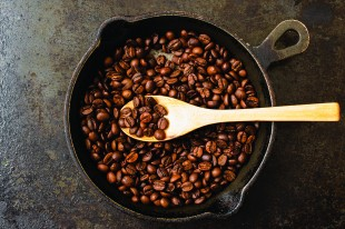 Sample spoon roasting coffee beans in a pan. Top view